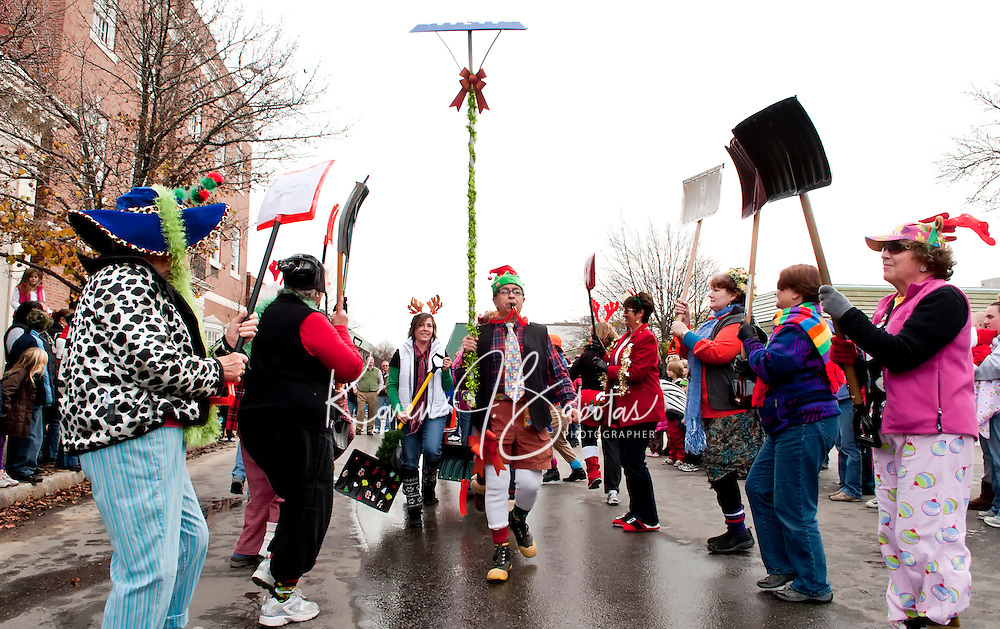 2011 Grand Marshall Larry Frates leads the N.H. Snow Shovel Brigade down Main Street on Saturday during the annual Laconia Holiday Parade.   (Karen Bobotas/for the Laconia Daily Sun)