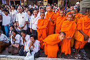 """03 FEBRUARY 2013 - PHNOM PENH, CAMBODIA:  People and novice Buddhist monks pray during the final Buddhist chanting service for former Cambodian King Norodom Sihanouk in the crematorium built for the King's funeral at the National Museum in Phnom Penh. Norodom Sihanouk (31 October 1922- 15 October 2012) was the King of Cambodia from 1941 to 1955 and again from 1993 to 2004. He was the effective ruler of Cambodia from 1953 to 1970. After his second abdication in 2004, he was given the honorific of """"The King-Father of Cambodia."""" He served as puppet head of state for the Khmer Rouge government in 1975-1976, before going into exile. Sihanouk's actual period of effective rule over Cambodia was from 9 November 1953, when Cambodia gained its independence from France, until 18 March 1970, when General Lon Nol and the National Assembly deposed him. Upon his final abdication in 2004, the Cambodian throne council appointed Norodom Sihamoni, one of Sihanouk's sons, as the new king. Sihanouk died in Beijing, China, where he was receiving medical care, on Oct. 15, 2012. His cremation will take place on Feb. 4, 2013. Over a million people are expected to attend the service.    PHOTO BY JACK KURTZ"""