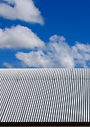 Blue sky and clouds over a corrugated tin roof. <br /> <br /> Editions:- Open Edition Print / Stock Image