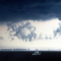 A Party (Head) fishing boat drifts in Raritan Bay (New York Harbor) as a severe thunderstorm passes by the areas with strong winds, rain and lightning.