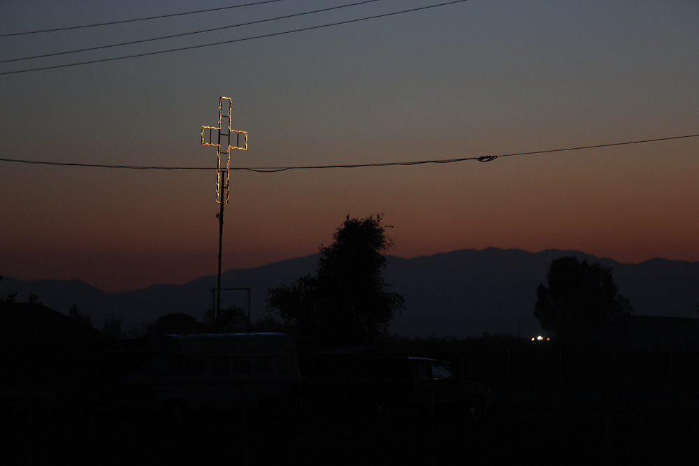 Dawn in the Central Valley, near Fresno. The most productive farmland in the world supports a vast industry of farm hands, pickers, sorters, packers, irrigation and water delivery specialists, laborers and growers.  Churches rise from the desert floor. <br /> Services in Spanish and English. April 13, 2015.