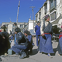 CHINA, TIBET. Tibetan Buddhist pilgrims circle Lhasa's Jokhang Temple through the Barkhor Bazaar (1986).