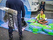 23 NOVEMBER 2012 - BANGKOK, THAILAND: A Thai riot police talks to a  vendor during training for a large anti-government protest in Bangkok Friday. Thai authorities have imposed the Internal Security Act (ISA), that enables police to call on the army if needed to keep order, and placed thousands of riot police in the streets around Government House in anticipation of a large anti-government protest Saturday. The group sponsoring the protest, Pitak Siam, said up to 500,000 people could turn out to protest against the government. They are protesting against corruption in the current government and the government's unwillingness to arrest or pursue fugitive former Prime Minister Thaksin Shinawatra, deposed in 2006 coup and later convicted on corruption charges. The current Thai Prime Minister is Yingluck Shinawatra, Thaksin's sister.       PHOTO BY JACK KURTZ