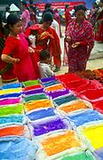 Hindu women buy brightly coloured dyes used for Hindu religious ceremonies. Pashupatinath, Kathmandu, Nepal