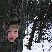 Seven-year-old Colter Smith peers out of a blind near a Great Gray Owl nest. Montana