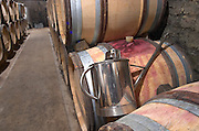 Topping up can. Oak barrel aging and fermentation cellar. Domaine Bertagna, Vougeot, Cote de Nuits, d'Or, Burgundy, France