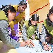 CAPTION: The Mahila Samakhya girls have split up into groups to draw the physical changes that occur in male and female bodies during adolescence. This is done pictorially, because this makes it easier for them to memorize. LOCATION: Mahila Samakhya, Ratu (block), Ranchi (city), Jharkhand (state), India. INDIVIDUAL(S) PHOTOGRAPHED: From left to right: Moni Suren, Rajni Lakra, Tara Among and Roshni Hembrom.