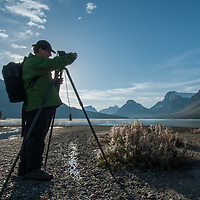 A photographer shoots beside Bow Lake in Banff National Park.  Behind are (L to R)  Mount Andromache, Mount Hector, Bow Peak, and Bow Crow Peak.