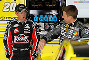 NASCAR Sprint Cup Series driver Matt Kenseth, left, reacts as he talks with fellow racer Jamie McMurray, right, before a morning practice at Kansas Speedway in Kansas City, Kan., Saturday, Oct. 17, 2015. (AP Photo/Colin E. Braley)
