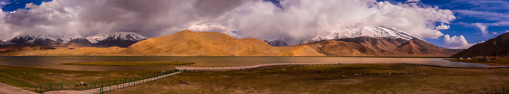 Panoramic view of Lake Karakul  (11,811 feet) is the highest lake of the Pamir plateau, near the junction of the Pamir, Tian Shan and Kunlun mountain ranges. Surrounded by mountains which remain snow-covered throughout the year, the three highest peaks visible from the lake are Muztagh Ata (24, 757 ft.) Kongur Tagh (25,025 ft.) and Kongur Tiube (24,704 ft.).The Karakoram Highway passing through the Pamir Mountains in Xinjiang China. It is the highest paved international road in the world; it connects Western China and Pakistan. It is one of the very few routes that cross the Himalayas and the most westerly of them. Historically, this was a caravan trail, one branch of the ancient Silk Road.
