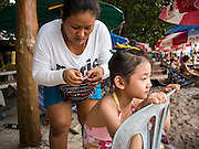 30 JULY 2013 - KOH SAMET, RAYONG, THAILAND: A girl has her braided on Ao Phia beach on Koh Samet island. This part of the island was not impacted by the oil spill that fouled the west side of the island. About 50,000 liters of crude oil poured out of a pipeline in the Gulf of Thailand over the weekend authorities said. The oil made landfall on the white sand beaches of Ao Prao, on Koh Samet, a popular tourists destination in Rayong province about 2.5 hours southeast of Bangkok. Workers from PTT Global, owner of the pipeline, and up to 500 Thai military personnel are cleaning up the beaches. Tourists staying near the spill, which fouled Ao Prao beach, were evacuated to hotels on the east side of the island, which was not impacted by the spill. PTT Global Chemical Pcl is part of state-controlled PTT Pcl, Thailand's biggest energy firm.      PHOTO BY JACK KURTZ