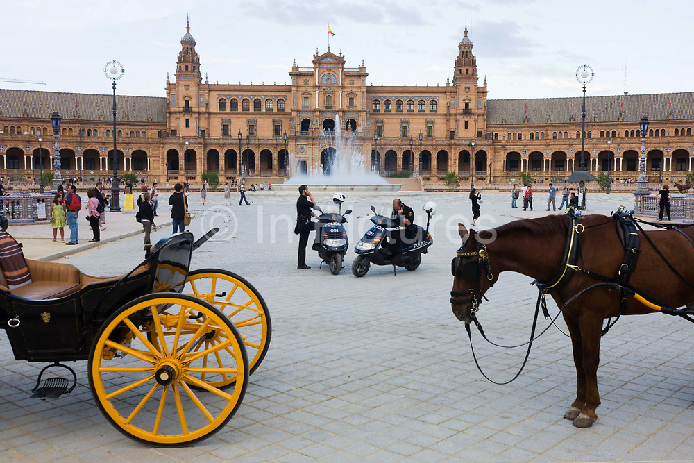 City policemen make calls from their scooters near horse and carriages in Seville's Plaza de Espana. With tourist horse carriages and visitors nearby, the two officers position themselves in the middle of this semi-circular enclosure built by Aníbal González, the great architect of Sevillian regionalism, for the Ibero-American exposition held in 1929. Today the Plaza de España mainly consists of Government buildings. The Seville Town Hall, with sensitive adaptive redesign, is located within it. The Plaza's tiled 'Alcoves of the Provinces' are backdrops for visitors portrait photographs, taken in their own home province's alcove.