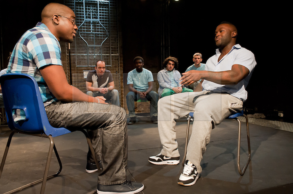 """© Copyright licensed to London News Pictures. 12/11/2010. """"Inside"""" by Philip Osment, presented by Playing Out at the Roundhouse, Camden, London. Based on the real experiences of young fathers in prison, the play deals with big questions surrounding relationships, both with their own fathers and with their children. Front L to R: Andre Skeete, Segun Olaiya. Back L to R: Jim Pope, Michael Amaning, Tarkan Cetinkaya, Jacob James Beswick."""