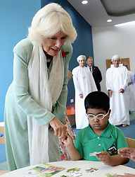 The Duchess of Cornwall watches a boy completing a puzzle as she visits Oman's first children's public library in Muscat during the royal tour of the Middle East.