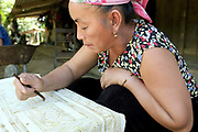A Hmong ethnic minority woman decorates woven hemp fabric by batik, a wax resist technique, Vieng Hang, Houaphan province, Lao PDR. Bees wax is collected from the forest, heated in small metal pots and mixed with indigo paste (which colours the wax and makes it easier to see on the cloth). A bamboo pen with a metal nib is used for drawing the wax onto the hemp. The wax marks will resist the dye when the cloth is dipped in the indigo dye bath and left to dry. After the last dye bath has been completed, the cloth is boiled to remove the wax. The resulting fabric is an indigo blue colour with white designs and is the base for cotton applique and colourful embroidery. Making hemp fabric is a long and laborious process which the Hmong women make into skirts for their traditional clothing. In Lao PDR, hemp is now only cultivated in remote mountainous areas of the north.