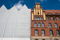 Exterior view of Szczecin Filharmonia concert hall contrasting with traditional architecture of adjacent building in Szczecin , Poland.