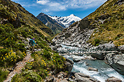 A hiker crosses Snowy Creek on the descent from Rees Saddle to Dart Hut on the Rees-Dart Track in Mount Aspiring National Park, Otago region, South Island of New Zealand. Glacier-clad Mt Edward rises above.