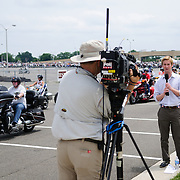A TV reporter broadcasts a feed in front of the riders departing for the annual Rolling Thunder motorcycle rally through downtown Washington DC on May 29, 2011. This shot was taken as the riders were leaving the staging area in the Pentagon's north parking lot, where thousands of bikes and riders had gathered.