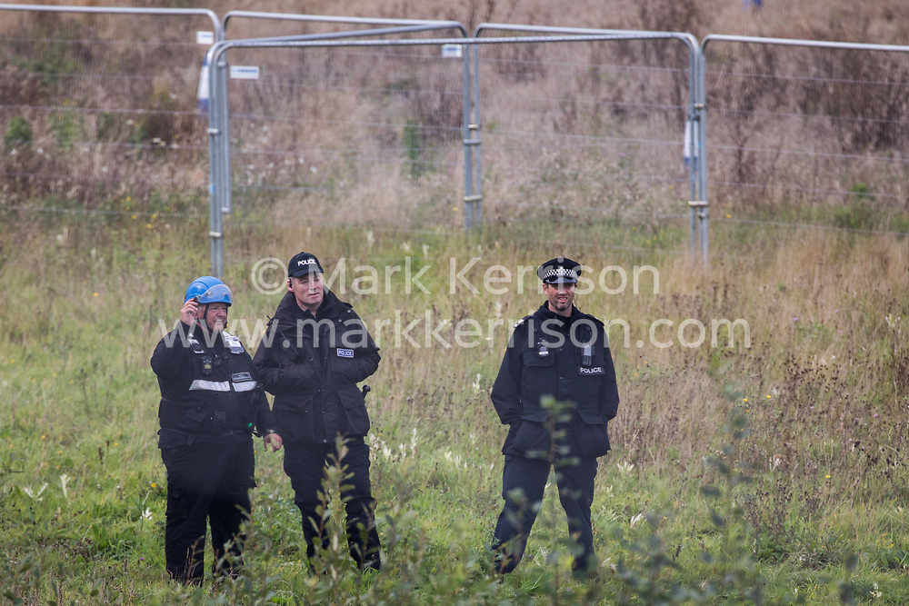Steeple Claydon, 23rd September, 2020. A National Eviction Team enforcement agent and Thames Valley Police officers watch tree surgeons working on behalf of HS2 Ltd fell a 200-year-old oak tree alongside the East West Rail route known locally as the '7 Sisters Oak' as part of works connected to the HS2 high-speed rail link. A small group of local people and anti-HS2 activists based at the nearby Poors Piece Conservation Project also observed the felling of the tree, which was home to bats and other species, whilst monitored by a joint force of around fifty bailiffs, security guards and police officers from Thames Valley Police.