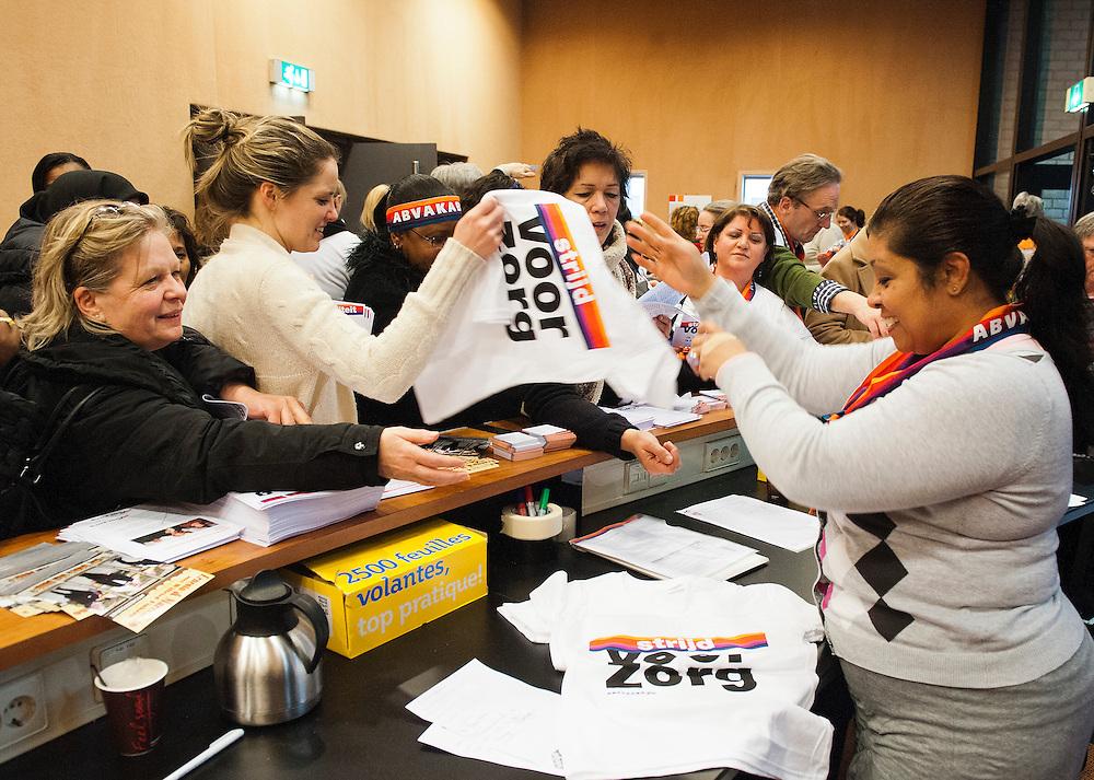 Nederland, Utrecht, 14 febr 2012.Jaarbeurs, Unieke bijeenkomst medewerkers cao VVT voor zorg..Een zaal vol leden van Abvakabo FNV als voorbereiding op akties als de coa onderhandelingen binnen de zorg weer gaan beginnen. De cao loopt op 1 maart af en de vooruitzichten voor zorg medewerkers zijn slecht. Er is een petitie waarvoor handtekeningen verzameld gaan worden, de handtekeningenlijsten werden aan het eind van de bijeenkomst uitgedeeld, alsmede de laatste aktie-t shirts die zeer gewild waren.Foto (c): Michiel Wijnbergh
