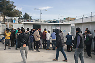 Asylum seekers stand outside an office to obtain Greek papers in the Moria refugee camp, Lesvos island, Greece.