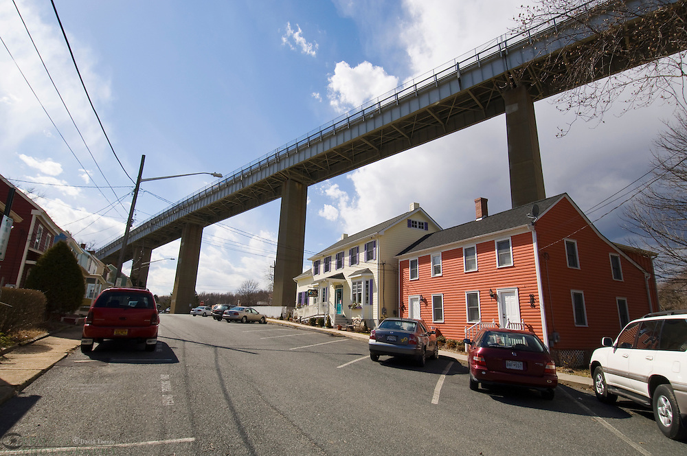 Chesapeake City, Maryland--The Chesapeake Country Scenic Byway, Route 213, towers over shops on Charles Street In Chesapeake City. The Bridge transends to cross the Chesapeake & Delaware Canal..