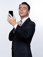 handsome caucasian man portrait checking cell phone isolated studio on white background wearing suit