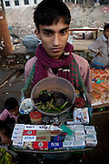 A street vendor sells cigarettes at the Sadarghat dock on the Buriganga River in Dhaka, Bangladesh.