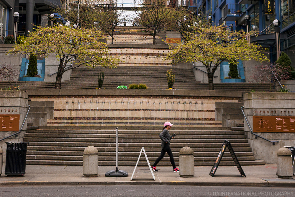 A woman speed walks in front of the empty Harbor Steps, an area of downtown that's typically filled with people socializing and lounging. (April 4, 2020).