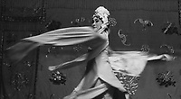 Chinese opera performer captured in movement on the stage.