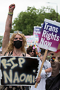 A protester holding a sign paying tribute to Naomi Hersi raises a fist as thousands of people take part in a London Trans+ Pride march from the Wellington Arch to Soho Square on 26th June 2021 in London, United Kingdom. London Trans+ Pride is a grassroots protest event which is not affiliated with Pride in London and focuses on creating a space for the London trans, non-binary, intersex and GNC community to come together to celebrate their identities and to fight for their rights.