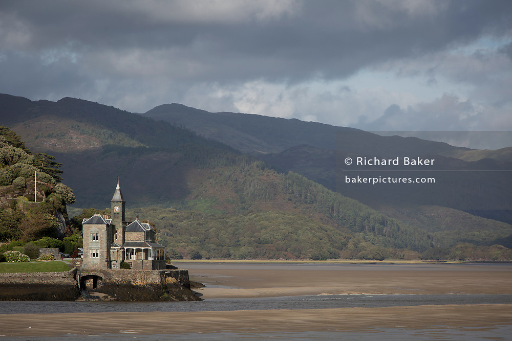 Seen from the Barmouth Bridge is Coes-Faen Spa Lodge, a former Victorian residence on the Mawddach estuary, on 13th September 2018, in Barmouth, Gwynedd, Wales. Coes Faen Lodge dates back to around 1865 and was built by the Lowe brothers, mill owners from the West Midlands, in the late 1800s, when the railway first came to the area and started the transformation of Barmouth (Abermaw) from a shipbuilding, fishing and trading rural community to a Victorian seaside resort destination.