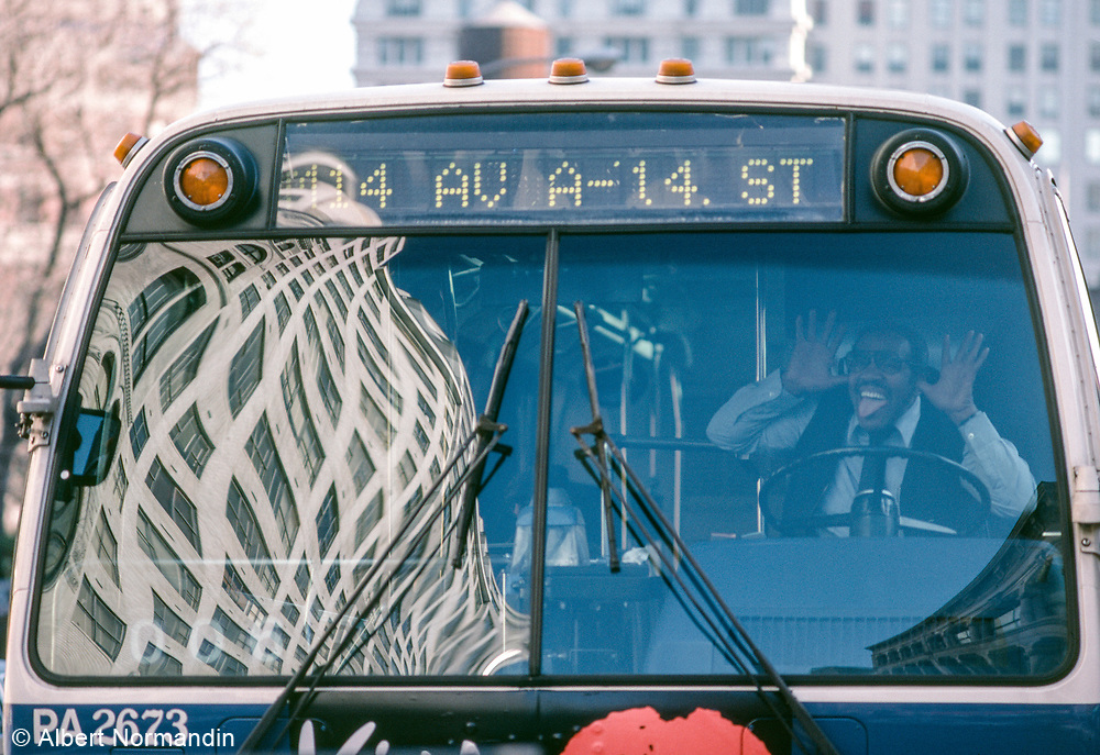 Bus driver making funny face with building reflection, 14th Street, New York City, New York, USA