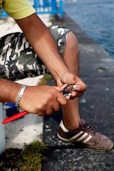 Un giovane pescatore fotografato nel porto di Brindisi mentre prepara l'esca per la sua battuta di pesca alle orate. Nel periodo di maggio e giugno questi sparidi si avvicinano verso le banchine per cibarsi di grossi molluschi come ad esempio le cozze.