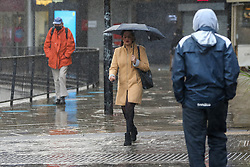 © Licensed to London News Pictures. 03/11/2020. London, UK. A woman shelters from heavy rainfall underneath an umbrella in north London. The Met Office forecasts rain and strong winds in the South East of England. Photo credit: Dinendra Haria/LNP