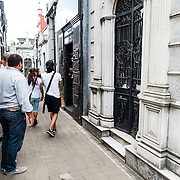 Visitors gather around the gravesite of Eva Peron, a former first lady of Argentina and beloved national figure. La Recoleta Cemetery is a famous cemetery in the Recoleta neighborhood of Buenos Aires and is famous for being the burial sites of Eva Peron, Argentinian presidents, and other notables. The cemetery features above-ground gravesites and crypts and is organized into a series of streets and boulevards.