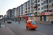 A strange looking orange single seat car and street scene in De Hui city, Jilin Province. North Eastern China.