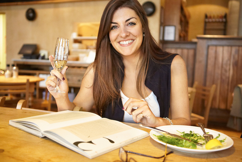 Portrait photograph of woman with smile holding champagne while having lunch at restaurant