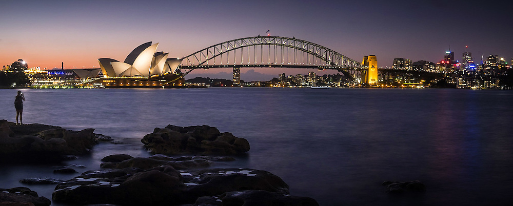 A woman takes a photograph of the Sydney Harbour Skyline at dusk.