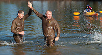 "Jaime Poire and Bill Peck from Team UPS ""high five"" after they plunge into Opechee Cove Saturday afternoon for the 8th annual Salvation Army Turkey Plunge.  (Karen Bobotas/for the Laconia Daily Sun)"