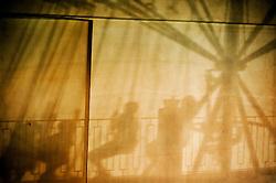 Peschici, ombra di una giostra riflessa sulla facciata di un palazzo
