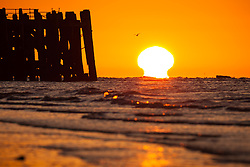 © Licensed to London News Pictures. 03/10/2016. Southsea, Hampshire, UK.  The sun bleeds into the horizon as it rises over the end of South Parade Pier in Southsea this morning, 3rd October 2016. People out enjoying the sunrise enjoyed a cool but clear morning on what is to be another dry and sunny autumn day in the south of England. Photo credit: Rob Arnold/LNP