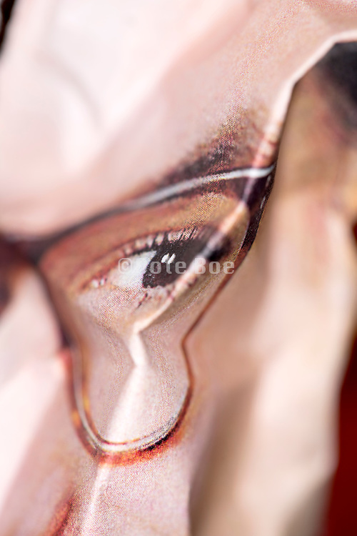crumpled page from a newspaper style print with cropped close up of a female eye wearing glasses