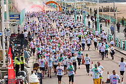 "© Licensed to London News Pictures. 23/09/2017. Brighton, UK. Thousands of participants run in the Brighton ""Color Run"" event. Runners get covered in coloured powder after each kilometre on the 5 kilometre course. Photo credit: Hugo Michiels/LNP"