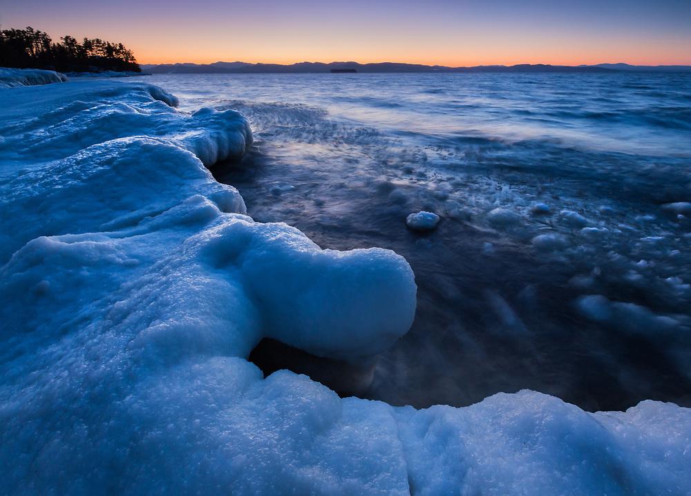 Mid winter scene at sunset along the icy shores of Lake Champlain at twilight.  Oakledge Park, Burlington, Vermont