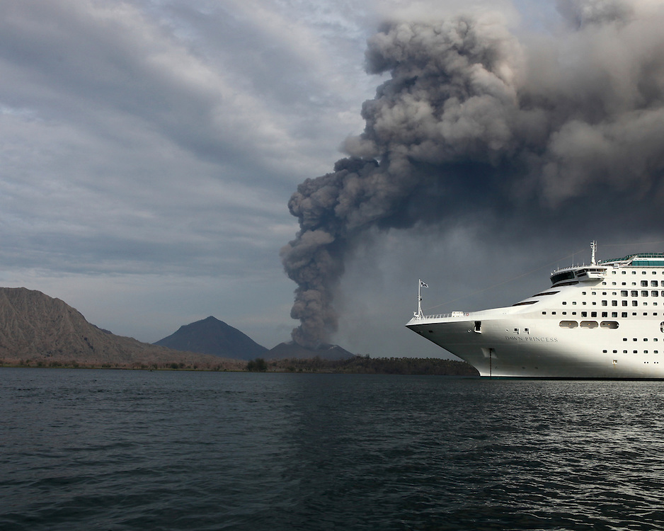 A cruise ship at anchor in Rabaul Harbour, Papau New Guinea. Smoke pours out of Tavurvur Volcano in the distance.