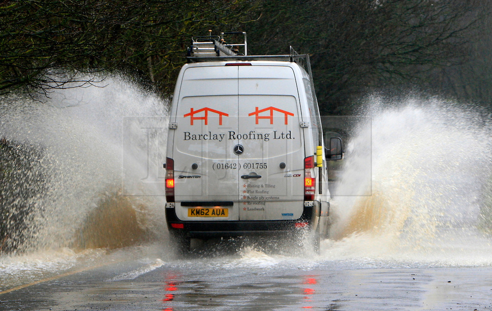 © London News Pictures. 06/01/2016. A car drives through flood waters on Fox Covert Lane, Ponteland, North east England. Large parts of the UK continue to suffer flooding after more heavy rain.  Areas of Northumberland and the North East have suffered with many being displaced from their homes as a result of flooding. Photo credit: Adam Davies/LNP