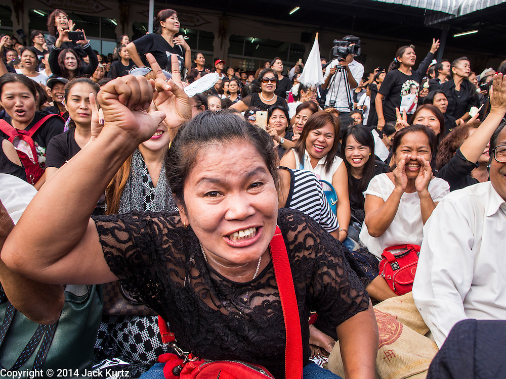19 OCTOBER 2014 - BANG BUA THONG, NONTHABURI, THAILAND:  People cheer for former Thai Prime Minister Yingluck Shinawatra at Apiwan Wiriyachai's cremation at Wat Bang Phai in Bang Bua Thong, a Bangkok suburb, Sunday. Apiwan was a prominent Red Shirt leader. He was member of the Pheu Thai Party of former Prime Minister Yingluck Shinawatra, and a member of the Thai parliament and served as Yingluck's Deputy Prime Minister. The military government that deposed the elected government in May, 2014, charged Apiwan with Lese Majeste for allegedly insulting the Thai Monarchy. Rather than face the charges, Apiwan fled Thailand to the Philippines. He died of a lung infection in the Philippines on Oct. 6. The military government gave his family permission to bring him back to Thailand for the funeral. His cremation was the largest Red Shirt gathering since the coup.    PHOTO BY JACK KURTZ