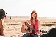 Pretty young girl playing guitar at the beach.