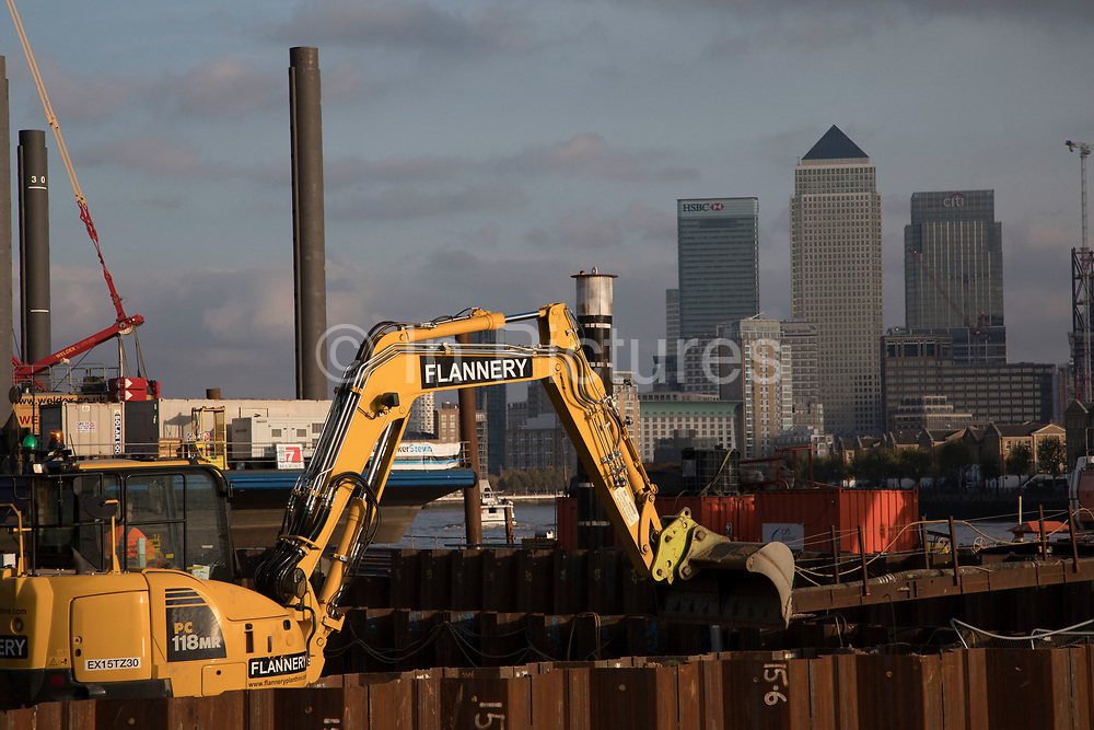 Construction work underway on the Thames Tideway Tunnel or Super Sewer on the River Thames near Wapping, with JCB diggers working in the foreground with Canary Wharf and the Docklands Financial District as the background in London, England, United Kingdom. The Thames Tideway Tunnel is an under-construction civil engineering project 25 km tunnel running mostly under the tidal section of the River Thames through central London, which will provide capture, storage and conveyance of almost all the combined raw sewage and rainwater discharges that currently overflow into the river.